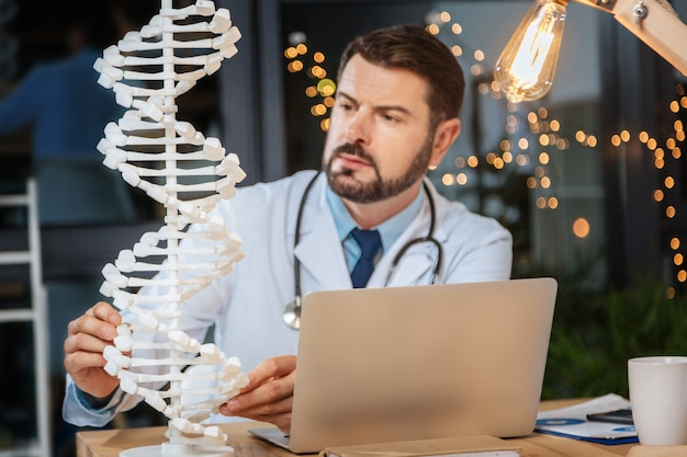Genomstudien. selektiver fokus eines dna-modells, das auf dem tisch steht, während es von einem netten professionellen männlichen wissenschaftler untersucht wird