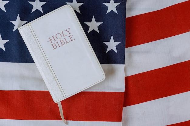 Geöffnete bibel mit einem religiösen heiligen buch über amerikanische flagge