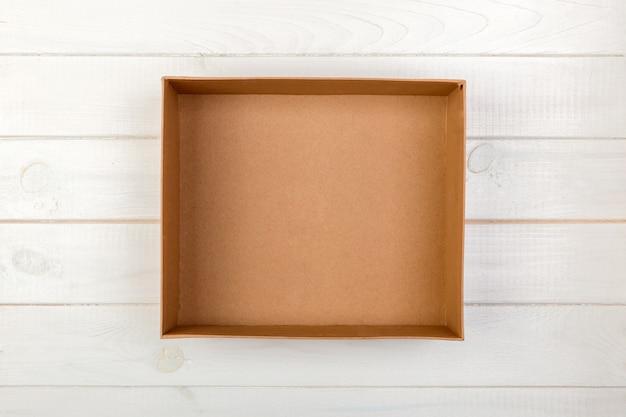 Geöffnete braune leere pappschachtel auf hölzernem hintergrund