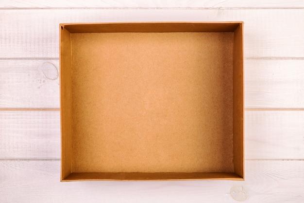 Geöffnete braune leere pappschachtel auf hölzerner, weinlese, getonte draufsicht