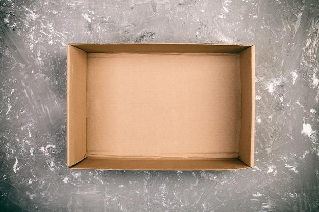 Geöffnete braune leere pappschachtel auf zementgrauoberfläche