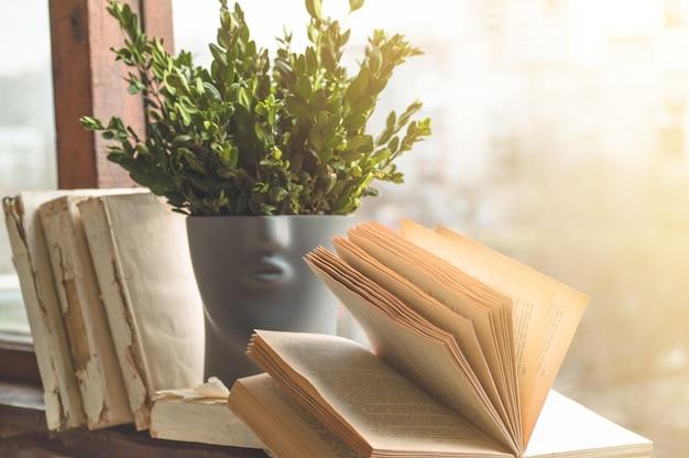 Geöffnete bücher auf vintage fensterbank mit einer schönen blumenvase.
