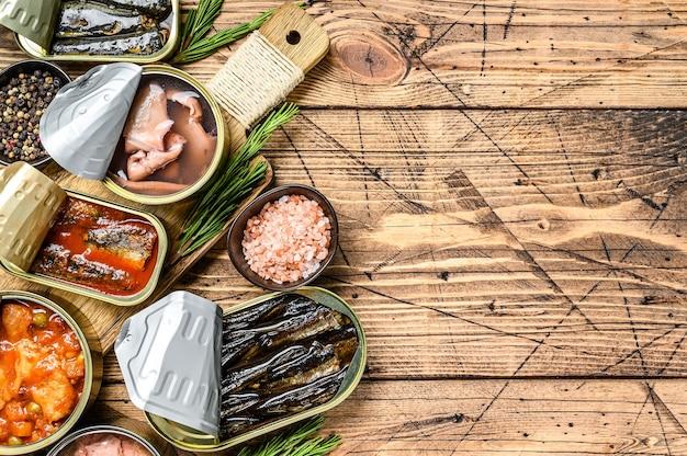 Geöffnete dosen mit saury, lachs, sprotten, sardinen, tintenfisch und thunfisch konservieren