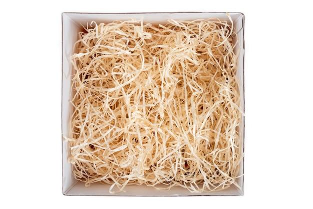 Geöffnete geschenkbox mit dekorativem strohhalm, füllstoff, spänen. draufsicht, leere geschenkbox lokalisiert auf weiß, modell für design.