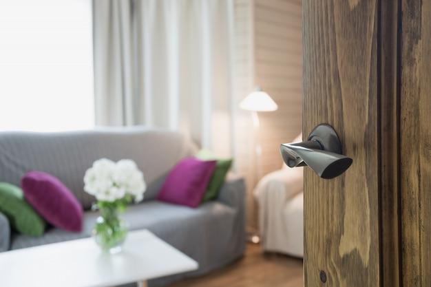 Geöffnete holztür zum modernen wohnzimmerinnenraum.