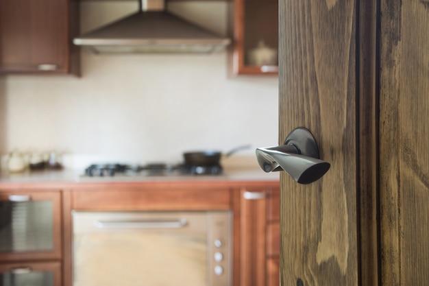 Geöffnete holztür zur küche mit pfanne auf dem herd.