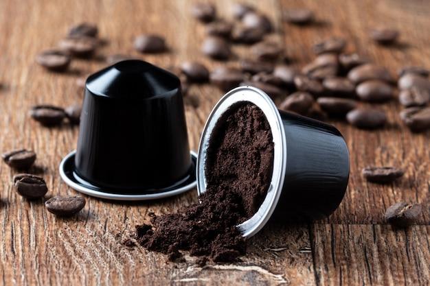 Geöffnete kaffeehülse auf holztisch oder capsula de cafe