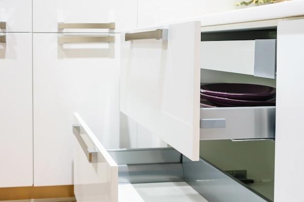 Geöffnete küchenschublade mit platten innen, eine intelligente lösung für die küche lagerung