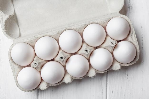 Geöffnete pappschachtel eier auf holztisch