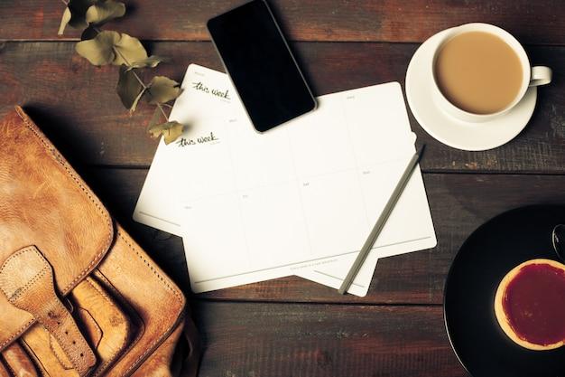 Geöffneter bastelpapierumschlag, herbstlaub und kaffee auf holztisch