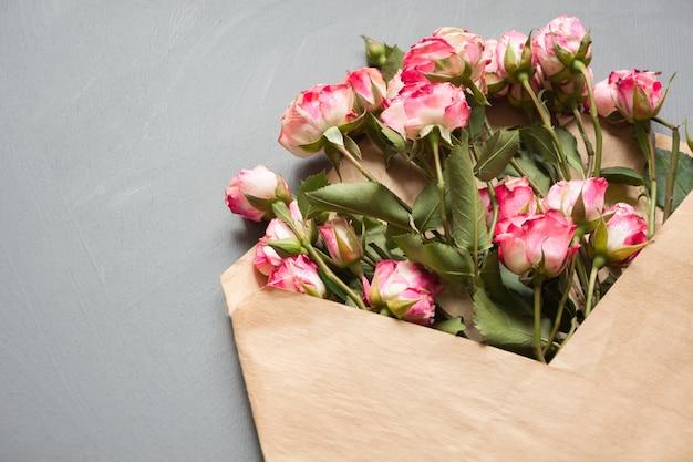 Geöffneter handwerksumschlag mit rosa rosen auf neutralem grau, draufsicht. festlich valentinstagskarte.
