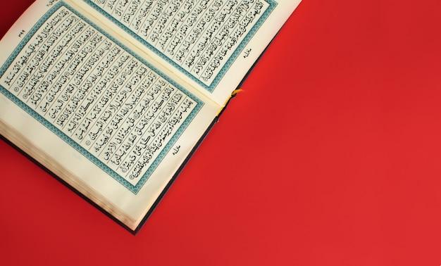 Geöffneter koran auf einem einfachen burgunderfarbenen raum