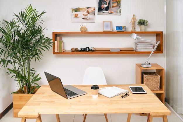 Geöffneter laptop, digitales tablet, planer und tasse kaffee auf tisch im modernen büro