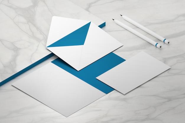 Geöffneter papierumschlag, visitenkarte und zwei stifte auf marmoroberfläche