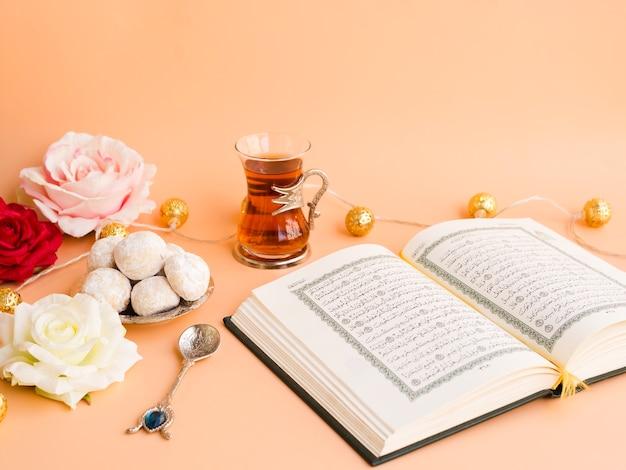 Geöffneter quran auf festlicher tabelle mit blumen