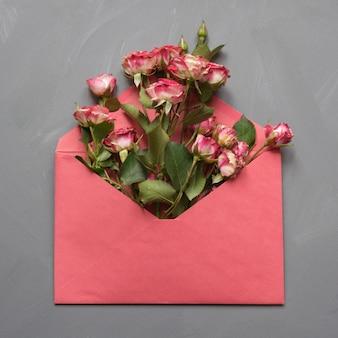 Geöffneter roter umschlag mit rosa rosen auf grau