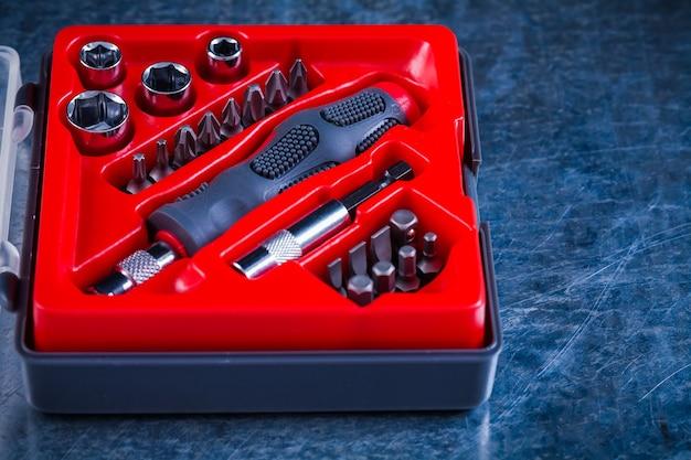 Geöffneter werkzeugkoffer mit schraubendreher und austauschbaren bits und köpfen auf metallkonstruktionskonzept.