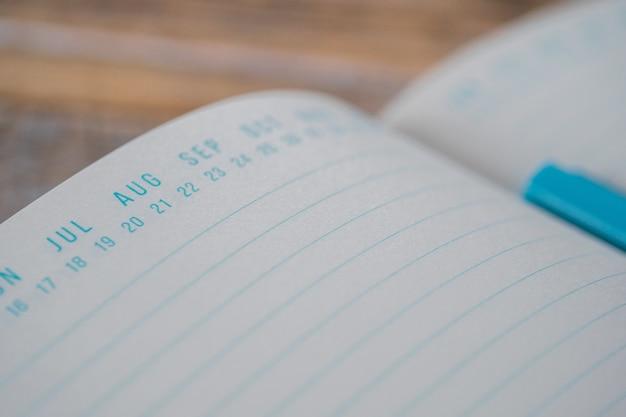 Geöffnetes blaues lehrbuch mit datumsmarkierungen oben auf einer holzoberfläche