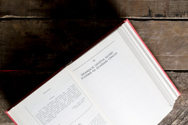 Geöffnetes buch auf hölzerner tischplatte