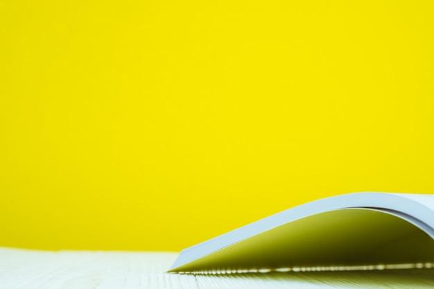 Geöffnetes buch auf weißer tabelle mit gelbem hintergrund.