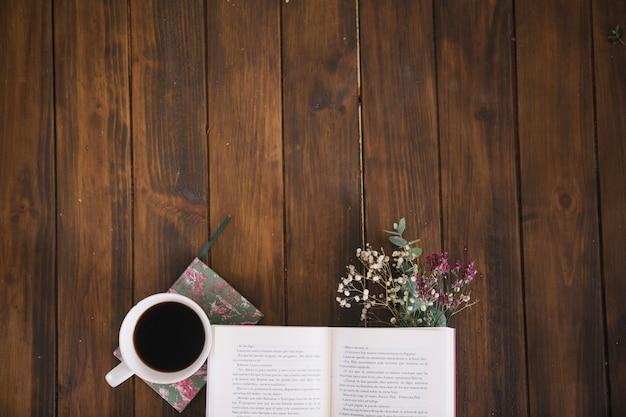 Geöffnetes buch und kaffee mit blumenstrauß