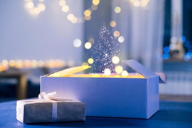 Geöffnetes geschenk, wunder und wünsche werden am heiligabend wahr. nahaufnahme des neujahrsgeschenks zu hause bei nacht. magischer hintergrund mit staub und lichtern, niemand