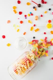 Geöffnetes glas in der nähe von verschütteten süßigkeiten