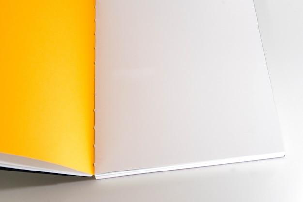 Geöffnetes leeres buch am weißen gelben designpapierhintergrund.