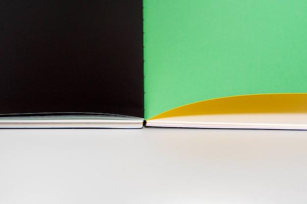Geöffnetes leeres buch am weißen schwarzen grünen designpapierhintergrund.