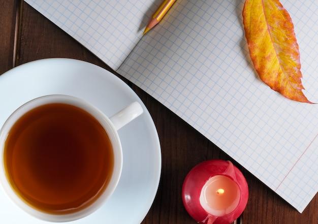 Geöffnetes leeres notizbuch mit karierten blättern mit einem bleistift neben einer tasse heißem tee auf braunem holzhintergrund