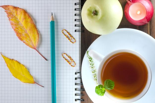 Geöffnetes leeres notizbuch mit karierten blättern mit einem bleistift neben einer tasse heißem tee