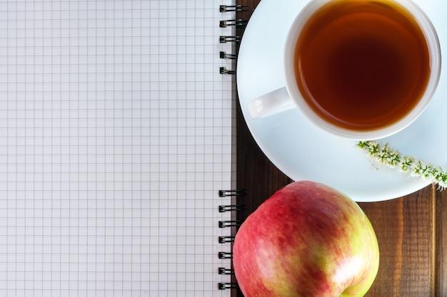 Geöffnetes leeres notizbuch mit karierten blättern neben einer tasse heißen tee