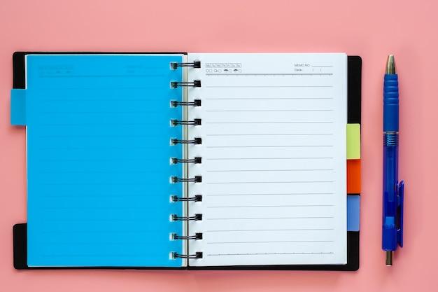 Geöffnetes leeres notizbuch mit stift auf rosa hintergrund