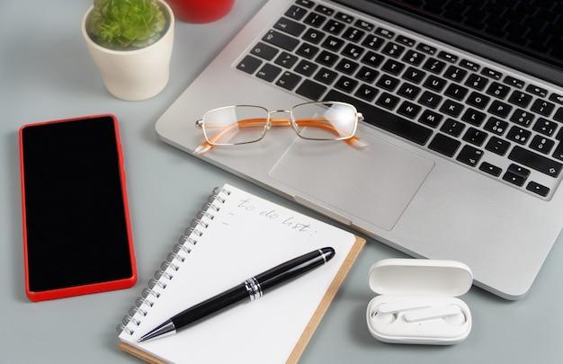 Geöffnetes lehrbuch mit handgeschriebener to do list in der nähe des laptops