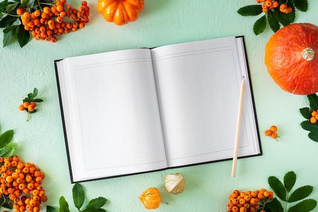 Geöffnetes notizbuch mit leeren seiten auf grünem hintergrund mit kürbissen, äpfeln und birnen. modell, ansicht von oben. herbstwohnung mit rezeptzutaten.