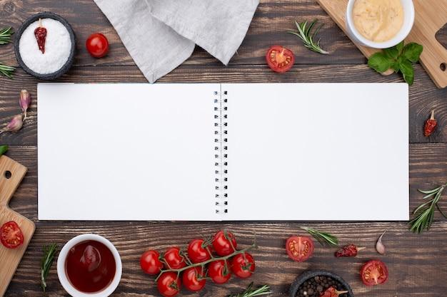 Geöffnetes notizbuch mit zutaten daneben auf dem tisch