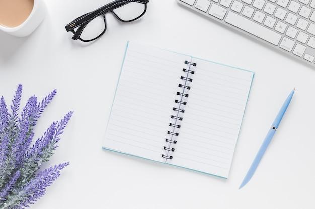 Geöffnetes notizbuch nahe lavendel, tastatur und gläsern auf schreibtisch