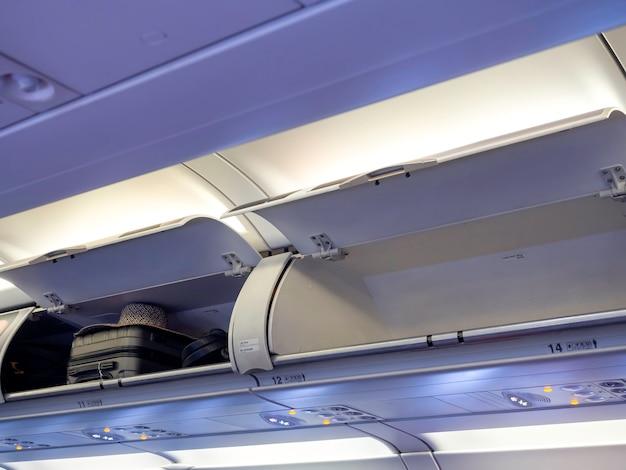 Geöffnetes schließfach über der sitzreihe nr. 12 und 14 in der kabine mit gepäck