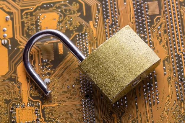 Geöffnetes vorhängeschloß auf computermotherboard. internet-datenschutzinformationssicherheitskonzept.