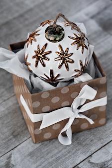 Geöffnetes weihnachtsgeschenk auf holztisch im dezember