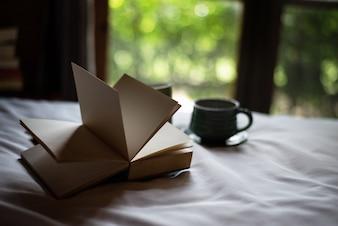 Geöffnetes Buch auf Bett gelegt