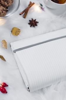 Geöffnetes Notizbuch auf weißer Abdeckung mit Dekorationen