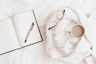 Geöffnetes Notizbuch mit Stift nahe Strickjacke mit Sachen auf Bedsheet