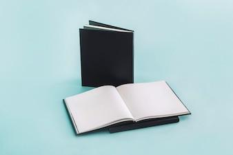 Geöffnetes Notizbuch nahe Notizblöcken mit schwarzer Abdeckung