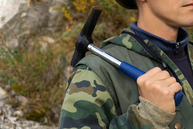 Geologe im freien hält einen geologischen hammer in der hand auf seiner schulter