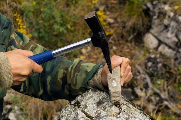 Geologe untersucht eine mineralogische probe mit hilfe eines geologischen hammers