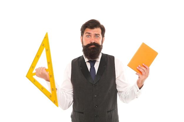 Geometrie interessant machen. schullehrer halten buch und dreieck. privatunterricht. der bärtige mann bereitet technische lehrmittel für den unterricht vor. geometrieunterricht. lehre und bildung.
