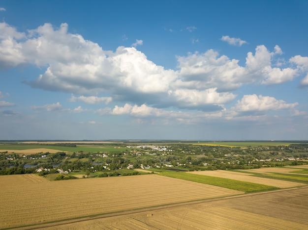 Geometrische abstrakte formen von landwirtschaftlichen feldern in grüngelben farben, landschaftslandschaft gegen blauen bewölkten himmel. eine vogelperspektive von der drohne.