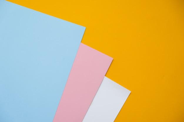 Geometrische ebene lage des blauen, gelben und rosa pastellfarbenpapiers