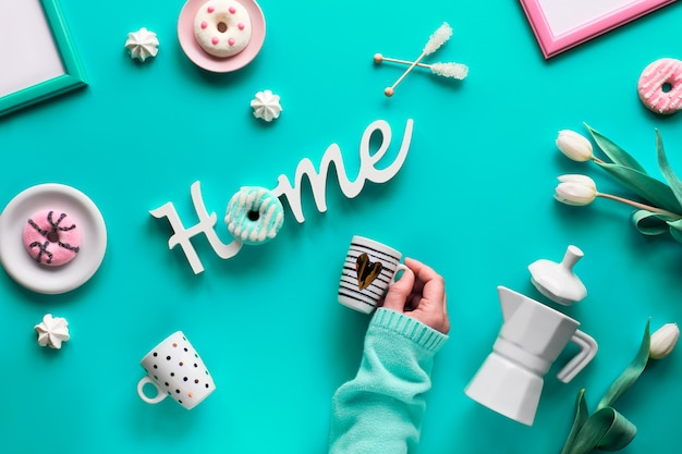 Geometrische frühlingswohnung lag in weiß und grün auf rosa hintergrund. ostern, muttertag, frühlingsgeburtstag oder jahrestag. kunststoff-heizbrett, ostereier, kaffeemaschine, tassen, tulpen, geschenke.